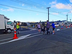 Traffic Management Staff help with the crossing of Onepu Rd