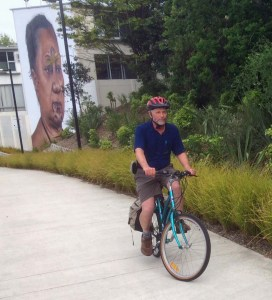 Wellinjgton cyclist rides the Grafton Cycleway under the watchful eye of a Tāmaki Makaurau kuia.